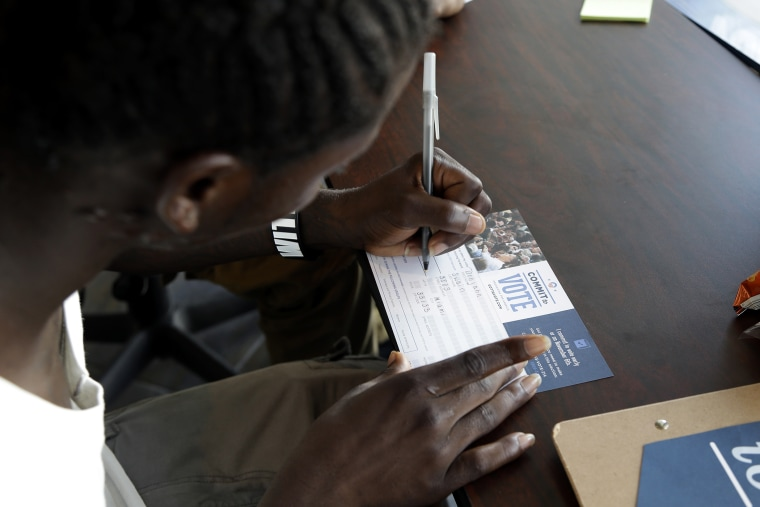 Dehjahn Swain, 19, signs a Commit To Vote card after registering to vote, Oct. 8, 2012 in Miami, Fla.