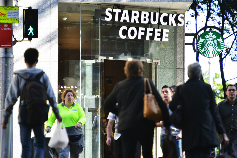Pedestrians cross a street in front of a Starbucks coffee house in Sydney on May 28, 2014.