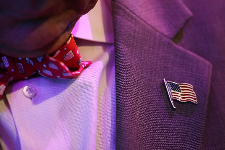 A man wears an American flag bowtie and lapel pin.