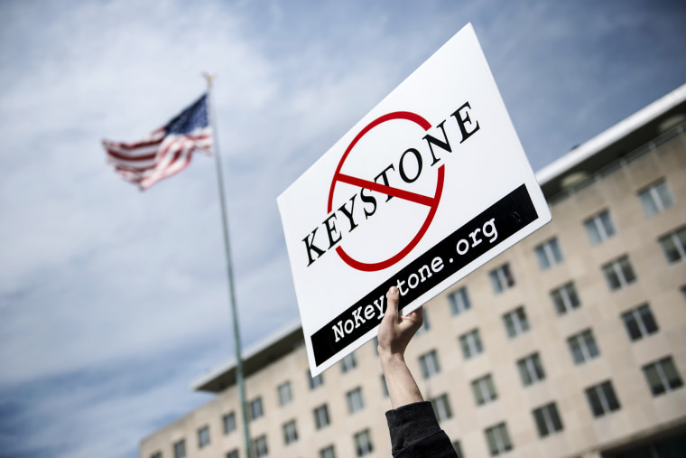 An activist holds up a sign outside the State Department during a protest of the Keystone XL pipeline on March 7, 2014 in Washington.