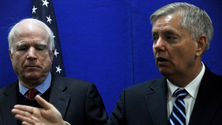 US Senator Lindsey Graham (R) speaks as Senator John McCain (L) looks on during a press conference at the US Embassy in Kabul on January 2, 2014.