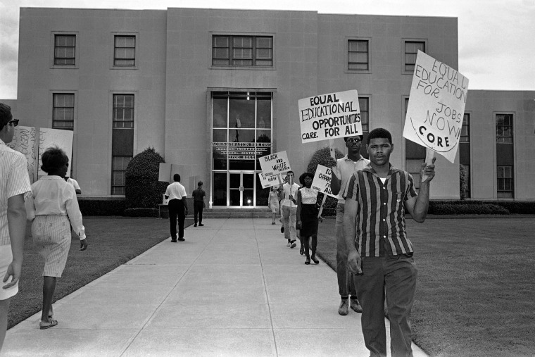 Members of CORE march in front of the administration building of the Dallas Independent School District carrying placards in Dallas, Texas on Aug. 26, 1964.