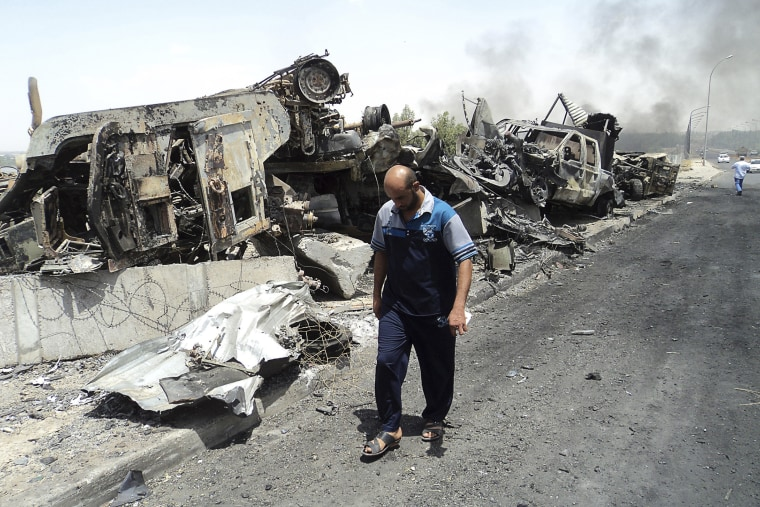 A man walks past near remains of burnt vehicles belonging to Iraqi security forces in the northern Iraq city of Mosul on June 13, 2014.