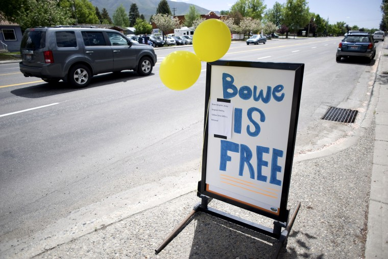 A car drives past yellow balloons and a sign of support for U.S. Army Sergeant Bergdahl in Hailey, Idaho