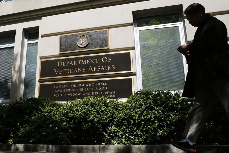The sign in the front of the headquarters building at the Department of Veteran Affairs is seen as a woman walks past in Washington, D.C., May 23, 2014.
