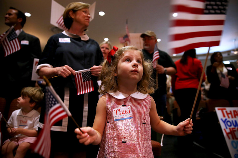 A young supporter of U.S. Sen Thad Cochran (R-MS) waves American flags during a campaign rally on June 23, 2014 in Jackson, Mississippi.