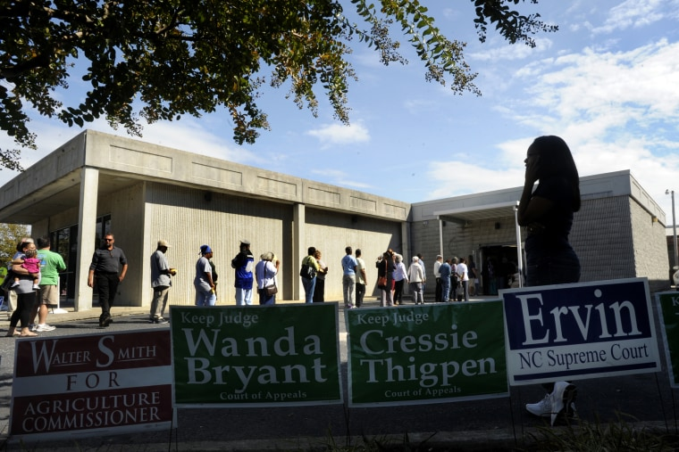 Campaign signs line the walk as people wait in line to vote in Wilson, North Carolina.