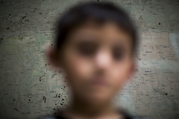 A Guatemalan child deported from the United State poses for photo in front of a map of the Guatemala City at an immigration shelter, June 19, 2014.