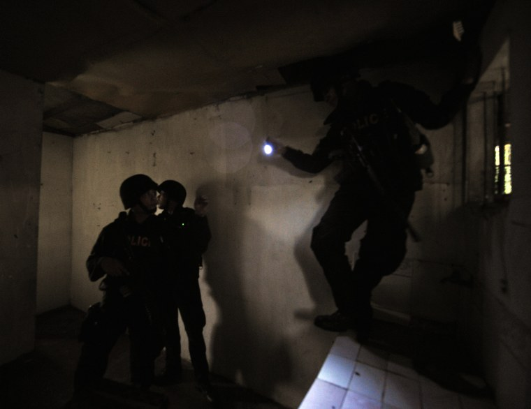 Members of SWAT team search a house for alleged gunmen.
