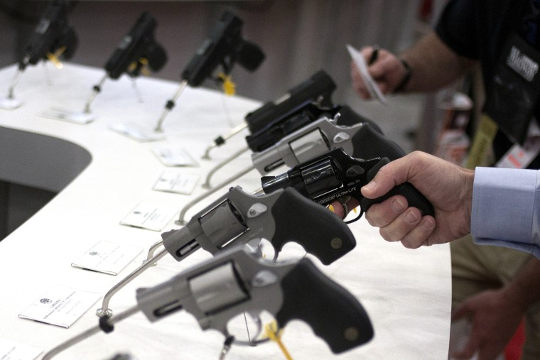 Man holds a gun in the exhibit hall of the George R. Brown Convention Center, the site for the NRA's annual meeting in Houston, Texas