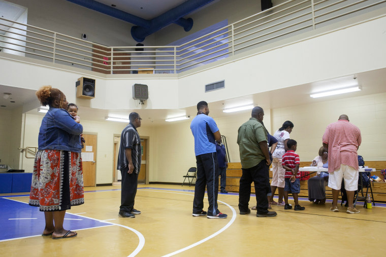 Voters wait in line to cast their ballot in a Republican primary runoff at the New Hope Baptist Church in Jackson, Miss., June 24, 2014.