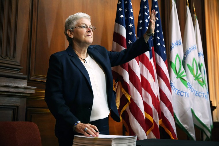 U.S. Environmental Protection Agency Administrator Gina McCarthy waves before signing new regulations for power plants at EPA headquarters June 2, 2014 in Washington, DC.