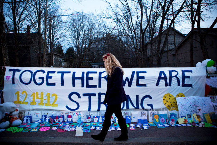A woman walks past a memorial for those killed in the school shooting at Sandy Hook Elementary School on December 24, 2012.