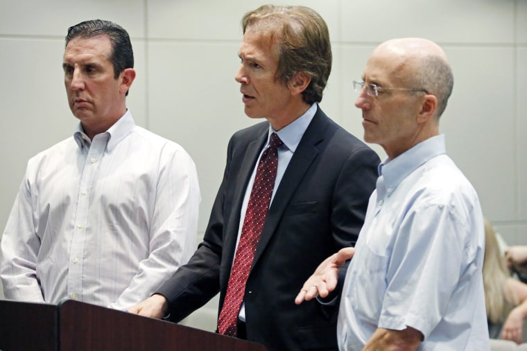 Mark Mayfield, a member of the board of the Central Mississippi Tea Party, right, listens as his attorney Merrida Coxwell, center, responds to questions, May 22, 2014, during an initial court appearance.