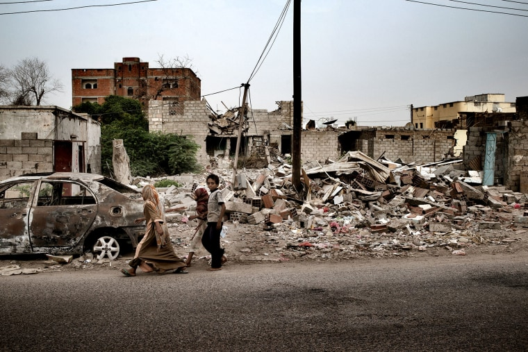 Civilians pass a house destroyed by a US drone strike in the town of Jaar, in the Abyan province of Yemen.