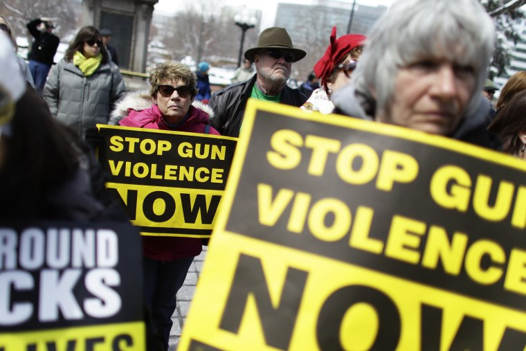 Community gun safety advocates and members of the public hold signs during a rally and vigil to honor victims of gun violence, sponsored by Colorado Ceasefire, on the steps of the Colorado State Capitol, in Denver, Thursday April 18, 2013.