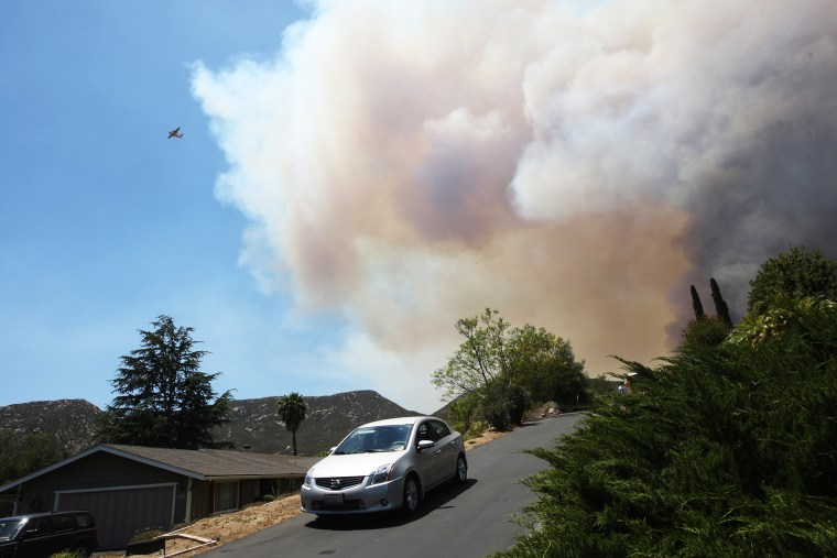 Smoke rises as the southeast flank of the Cocos fire bears down on houses near Del Dios Highway on May 15, 2014 near San Marcos, California.
