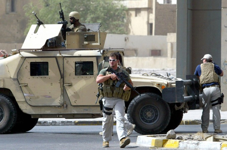 A picture taken on July 5, 2005 shows contractors of the U.S. private security firm Blackwater securing the site of a roadside bomb attack near the Iranian embassy in central Baghdad.