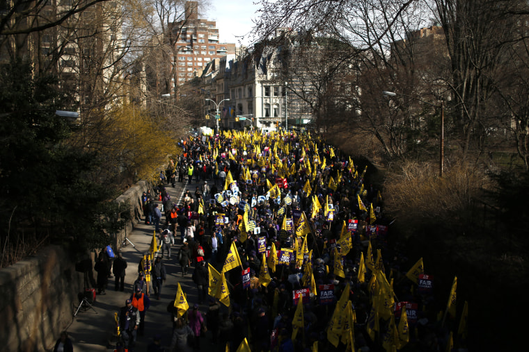 Members of the Service Employees International Union (SEIU) march out of Central Park onto 5th Avenue during a protest in New York City.