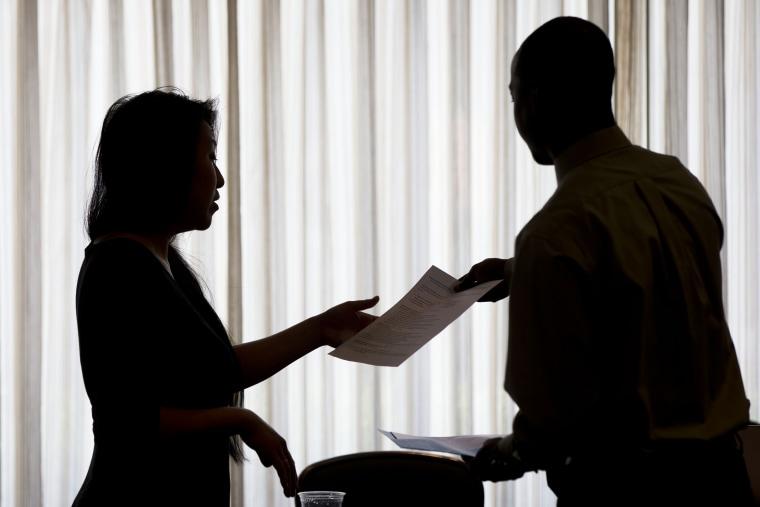 Recruiter Christina O takes an applicants resume during a job fair in Philadelphia, June 23, 2014.
