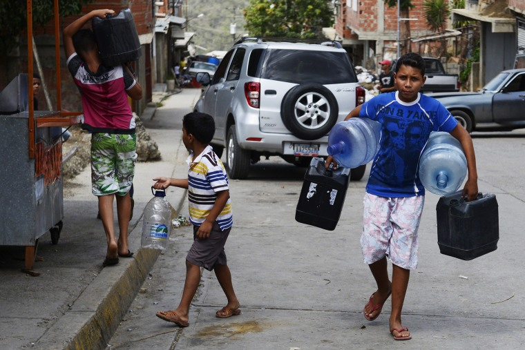 Boys carry empty bottles and cans to fill them with water in Caucaguita, Caracas, on June 20, 2014.