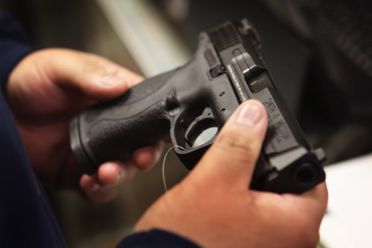 A customer shops for a pistol at a sporting goods store on Dec. 17, 2012 in Tinley Park, Ill.