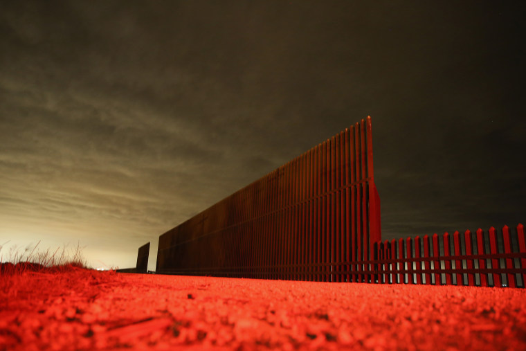 Lit by the tail light of a U.S. Border Patrol vehicle, a section of the U.S.- Mexico border fence stands on April 10, 2013 in La Joya, Texas.