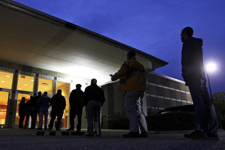Voters stand in line before sunrise to cast their votes at a polling precinct in Apex, N.C.