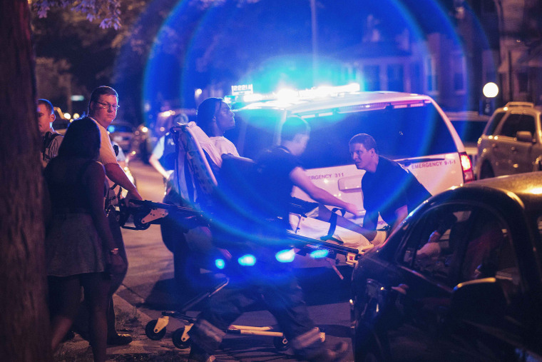 In this Sunday, July 6, 2014 photo, a man is wheeled on a stretcher after being shot in the leg on Chicago's South Side.