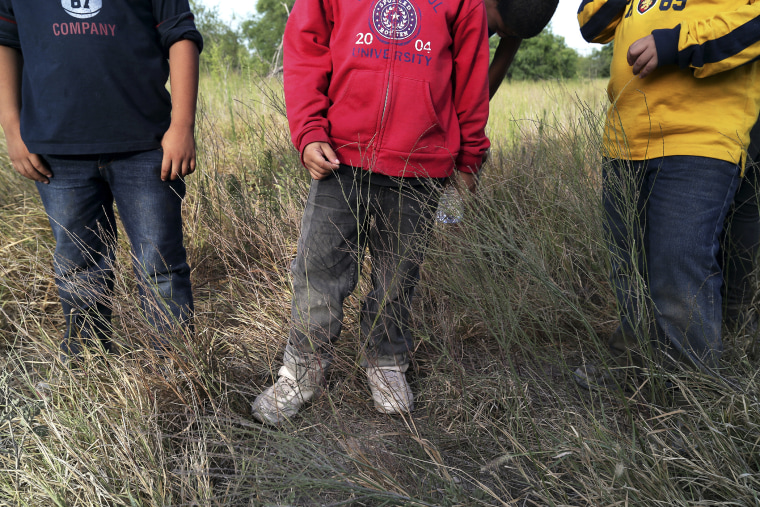 Three young boys wait as Border Patrol agents process a group of 22 migrants who have just crossed the Rio Grande near McAllen, Texas.