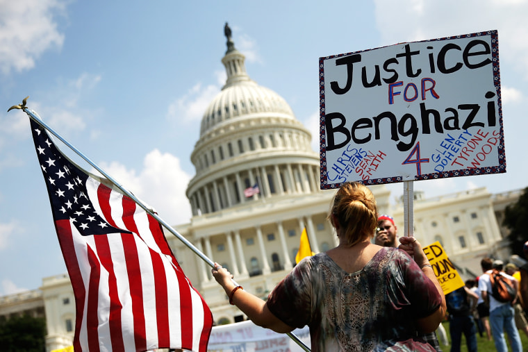 """A woman holds signs during a \""""Call to Action\"""" rally at the U.S. Capitol, marking the one year anniversary of the attacks on the U.S. compound in Benghazi, Sept. 11, 2013."""