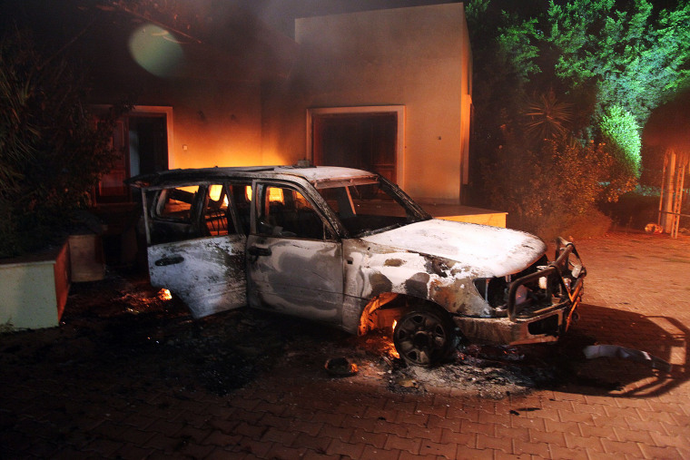 A vehicle and surrounding buildings smoldering after they were set on fire inside the US mission compound in Benghazi, September 11, 2012.