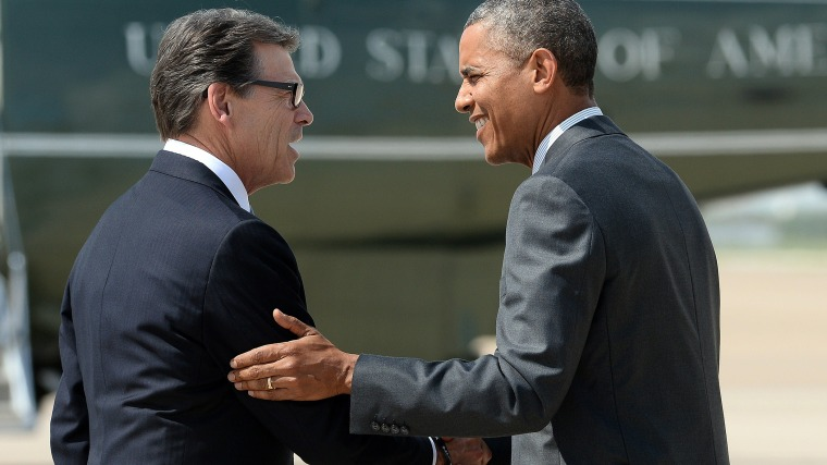US President Barack Obama is greeted by Texas Governor Rick Perry as he arrives in Dallas, Texas, on July 9, 2014