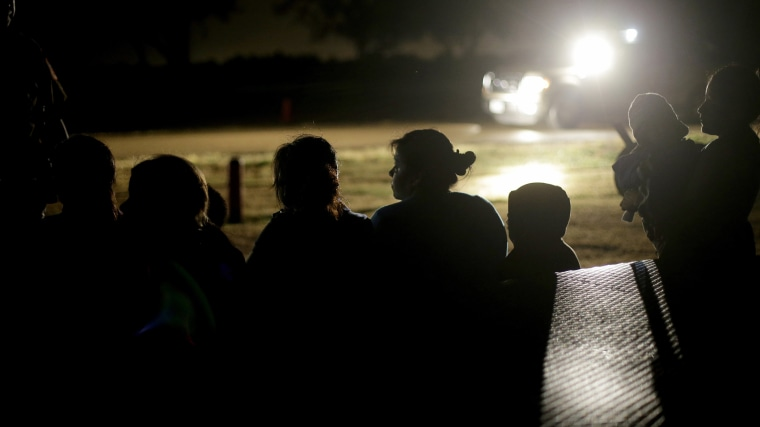 In this June 25, 2014 photo, a group of immigrants from Honduras and El Salvador who crossed the U.S.-Mexico border illegally are stopped in Granjeno, Texas.