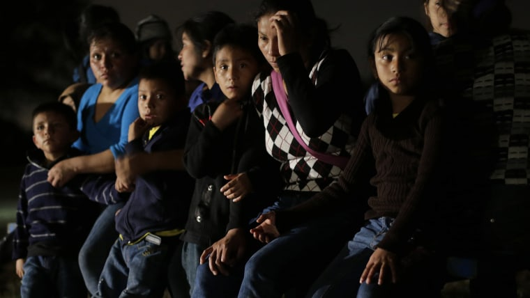 In this June 25, 2014 photo, a group of  immigrants from Honduras and El Salvador who crossed the U.S.-Mexico border illegally are stopped in Granjeno, Texas...