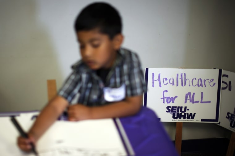 A boy draws signs at a health insurance enrollment event in Commerce, California March 31, 2014.