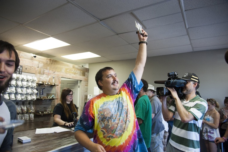 Mike Boyer turns to the crowd outside, showing off the 4 grams of marijuana he bought as the first in line to legally purchase marijuana in Spokane, Wash, July 8, 2014.