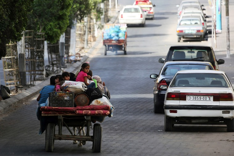 Palestinians flee their homes and head towards a United Nations' school to seek shelter in Gaza City, July 13, 2014.