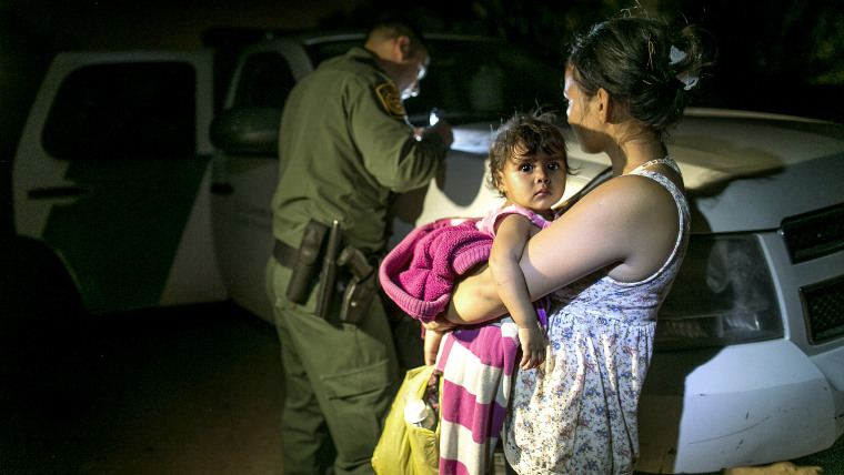 In this photo taken July 3, 2014, Flor Garcia, 19, of Honduras, holding her one-year-old daughter, Flor Fernandez, turned themselves over to Customs and Border Protection Services agents after crossing the Rio Grande from Mexico near McAllen, Texas.