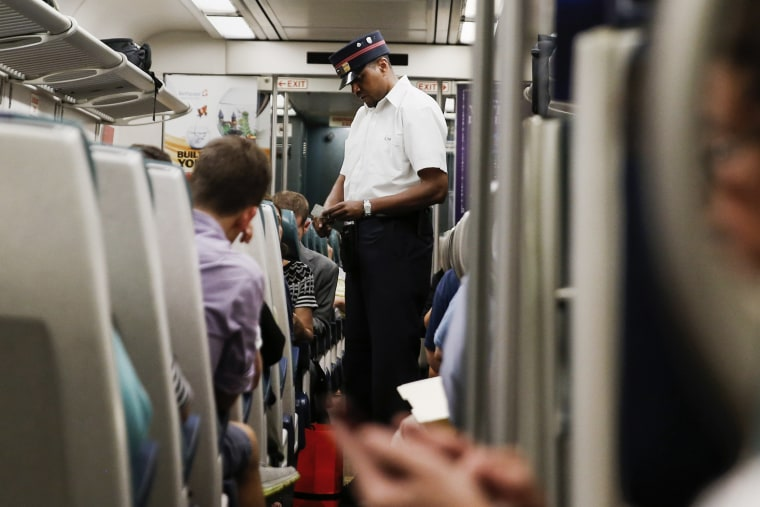 A Long Island Rail Road train conductor collects tickets aboard a train bound for Port Washington leaving Pennsylvania station in New York