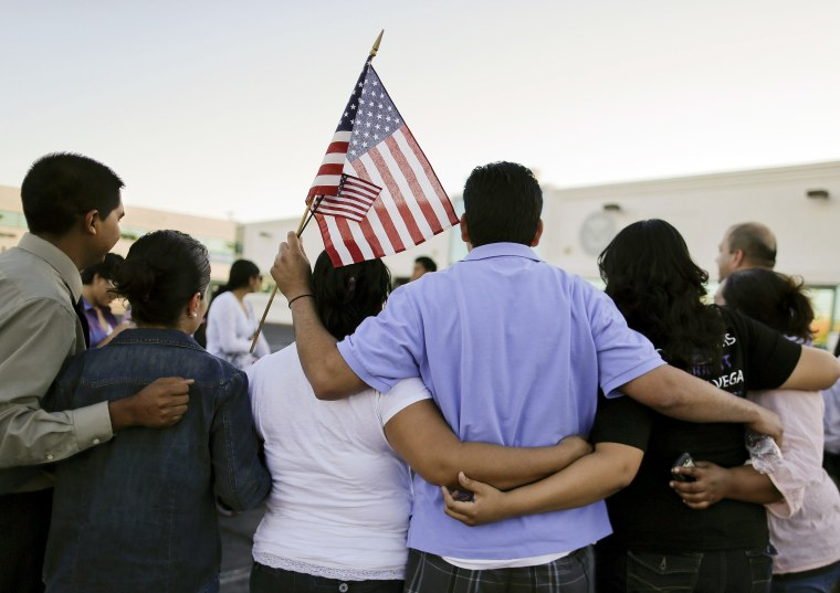 People gather for a photo outside the Immigration and Customs Enforcement offices during an immigration vigil, on April 10, 2013, in Las Vegas.