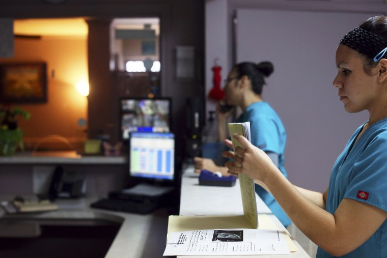 Medical assistant Nyla Munoz closes a walk-in patient's file at the Whole Women's Health Clinic in McAllen.
