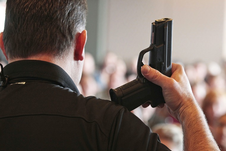 A firearm instructor holds a handgun up as he teaches a concealed-weapons training class to teachers in West Valley City, Utah.