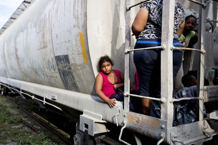 A young migrant girl waits for a freight train to depart on her way to the U.S. border, in Ixtepec, Mexico, July 12, 2014.