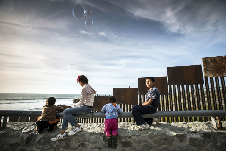 Children sit alongside the border fence beside the sea that divides Mexico from the United States, in Tijuana, Mexico.
