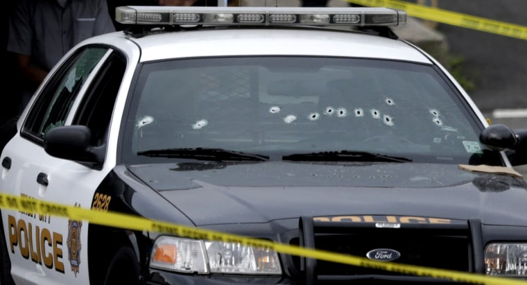 A Jersey City Police Department cruiser is seen with bullet holes on the windshield at the scene where an officer was shot and killed while responding to a call at a 24-hour pharmacy, Sunday, July 13, 2014, in Jersey City, N.J.