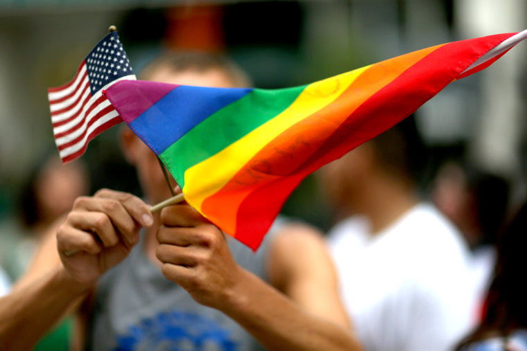 A protester holds an American flag and a rainbow flag.