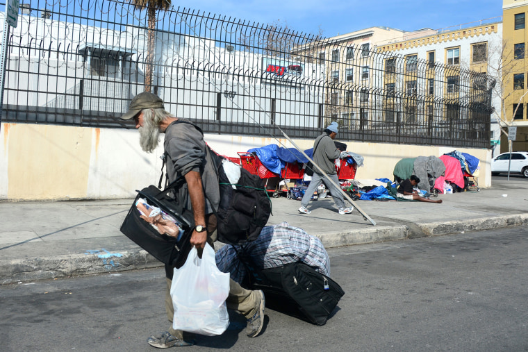 A homeless man carries his belongings in downtown Los Angeles, California, on January 8, 2014.