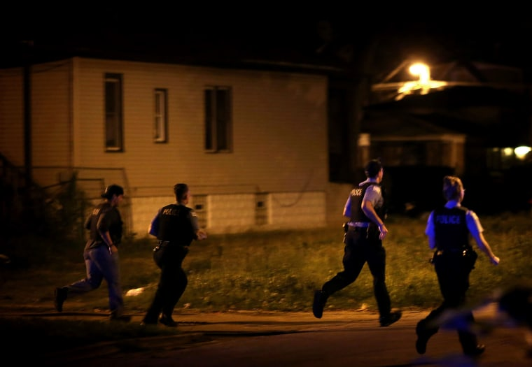 Chicago police respond to gunfire while searching for a gunman after finding three gunshot victims in the early hours of July 7, 2014, in Chicago.
