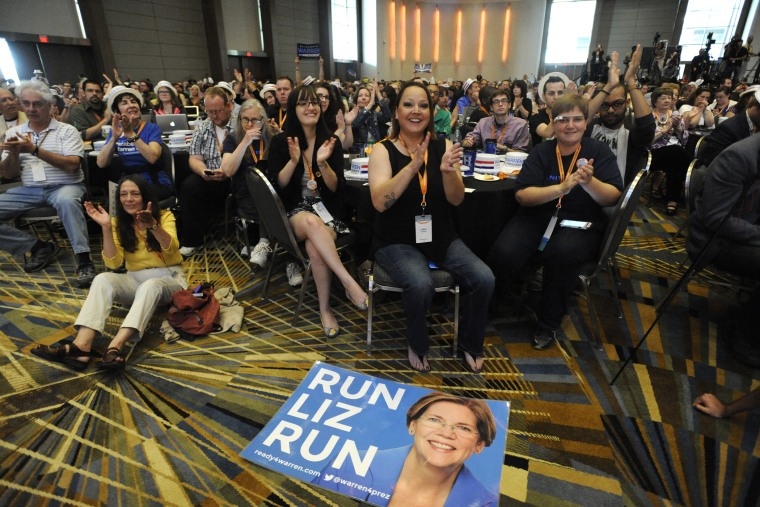 """A \""""Run Liz Run\"""" poster sits on the floor in front of LaNae Havens, center, as she cheers for Sen. Elizabeth Warren, D-Mass., at the Netroots Nation conference in Detroit, Mich., July 18, 2014."""